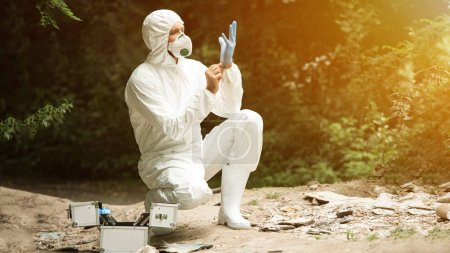 selective focus of male scientist in protective mask and suit putting on latex glove in forest