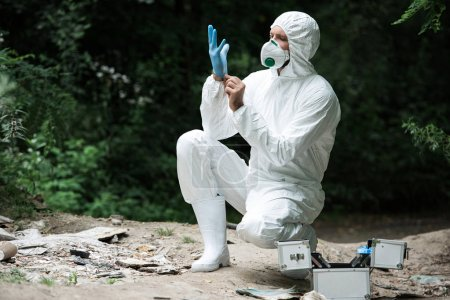 male scientist in protective mask and suit putting on latex glove in forest