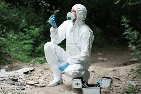focused male scientist in protective suit and mask examining stone while holding by tweezers in forest