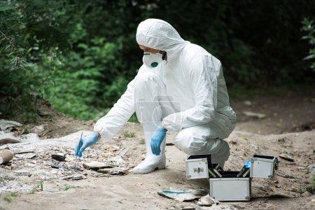 Photo pour Vue latérale du savant masculin en latex gants prise d'échantillon de Pierre de pincettes à l'extérieur - image libre de droit
