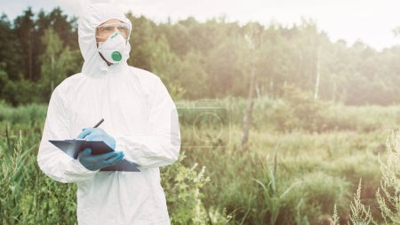 male scientist in protective mask, googles and suit looking away and writing in clipboard in meadow