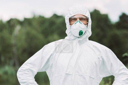 Photo pour Mise au point sélective du souriant scientifique mâle dans le masque et costume regardant la caméra à l'extérieur - image libre de droit