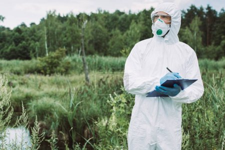 selective focus of male scientist in protective mask and suit writing in clipboard near water outdoors