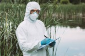 male scientist in protective mask and suit writing in clipboard near water outdoors