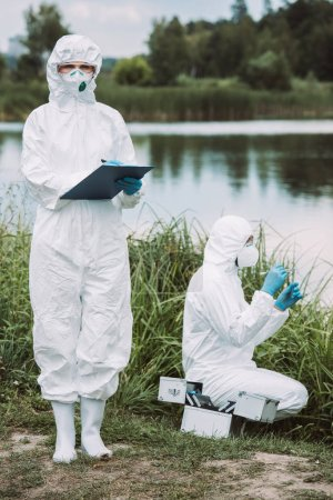 female scientist in protective mask and suit writing in clipboard while her colleague putting sample of water near river outdoors