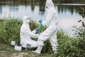 female scientist in protective mask and suit writing in clipboard while her colleague putting sample of water