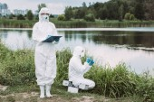 selective focus of female scientist in protective mask and suit writing in clipboard while her colleague putting sample of water near river outdoors