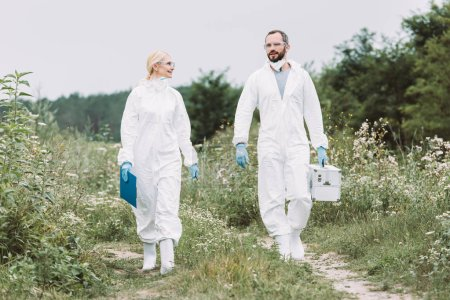 female and male scientists in protective suits walking with working suitcase and clipboard in meadow
