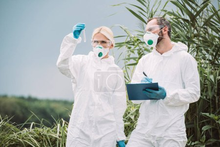 Photo for Male scientist in protective suit and mask writing in clipboard while his female colleague examining sample of water in test flask outdoors - Royalty Free Image
