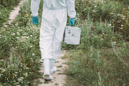 cropped image of male scientist in protective suit walking with working suitcase in meadow