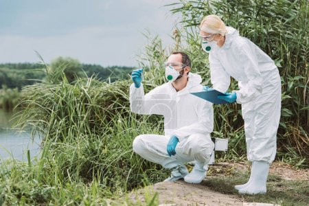 female scientist in protective suit and mask writing in clipboard while her male colleague examining sample of water in test flask