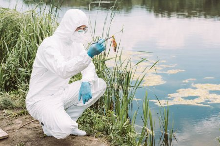 male scientist in protective suit and mask holding fish by tweezers near river