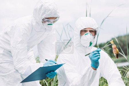 scientists in protective masks and suits examining fish and writing in clipboard outdoors