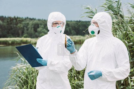 male scientist in protective mask and suit holding fish by tweezers while his female colleague writing in clipboard outdoors