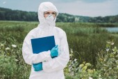 selective focus of female scientist in protective suit and googles holding clipboard in meadow