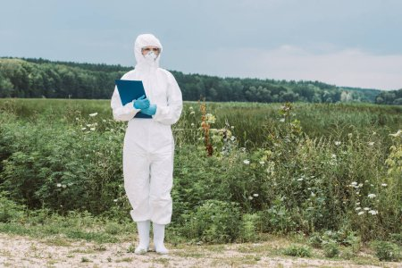 female scientist in protective suit and googles holding clipboard in meadow