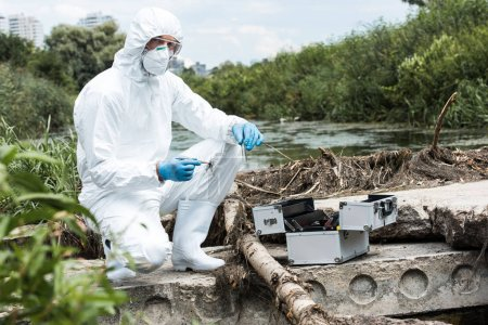 male scientist in protective suit holding sample of soil by tweezers and water in test flask outdoors