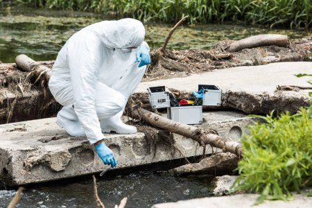 male scientist in protective suit and latex gloves taking sample of water in test flask outdoors
