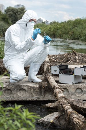 male scientist in protective suit and mask putting sample of soil by tweezers in test flask outdoors