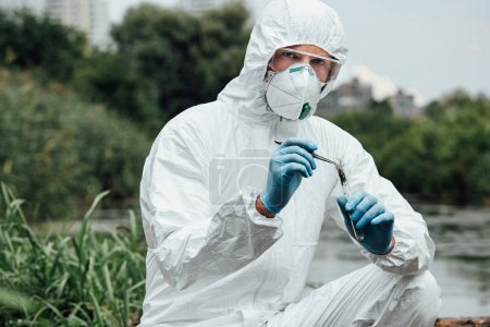 serious male scientist in protective suit and mask putting sample of soil by tweezers in test flask outdoors