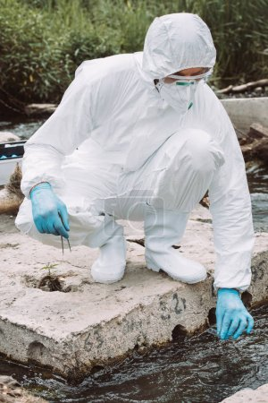 male scientist in protective suit and mask taking sample of water in test flask outdoors