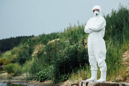 Photo for Male scientist in protective suit and mask standing near water outdoors - Royalty Free Image