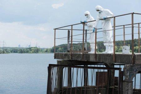 Photo pour Mâle scientifique en tenue de protection et masque pointant à l'eau à une collègue féminine avec plein air portable - image libre de droit
