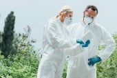 female and male scientists in protective masks and suits working with digital tablet outdoors