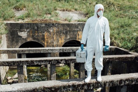 male scientist in protective mask and suit holding working suitcase near sewerage