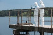male scientist in protective suit pointing on laptop screen to female colleague near river outdoors