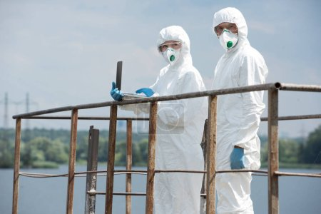 two scientists in protective suits and masks working with laptop and looking at camera near river outdoors