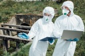 selective focus of female scientist with clipboard pointing to male colleague with laptop near sewerage