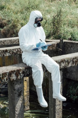 selective focus of male scientist in protective mask and suit writing in clipboard while sitting near sewerage