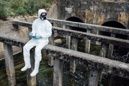 Photo pour Mâle scientifique au masque et costume écrit dans le presse-papiers en position assise près d'assainissement - image libre de droit
