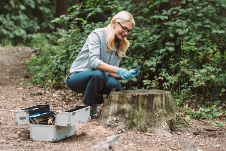 female scientist in latex gloves looking at twig by magnifier in forest