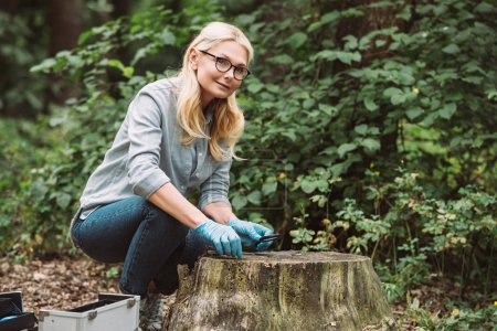 smiling female scientist in latex gloves sitting with tweezers and magnifier in forest