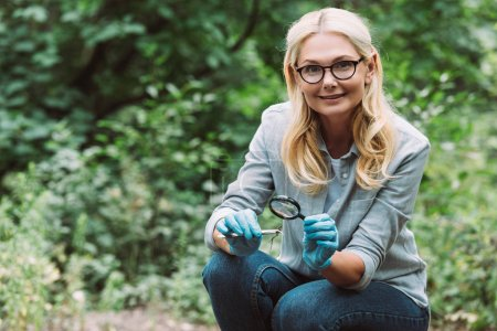 female scientist in latex gloves sitting with twig in tweezers and magnifier in forest