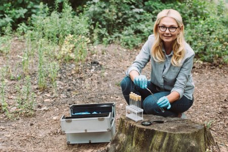 smiling female scientist putting twig by tweezers in test flask in forest