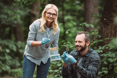 selective focus of male and female scientists examining and taking sample of dry leaf in forest