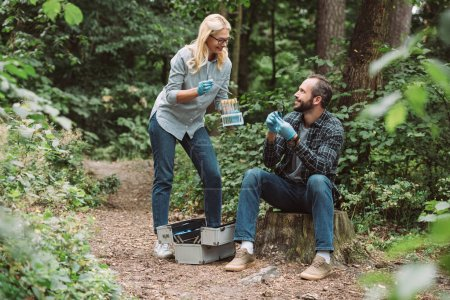 smiling male and female scientists examining and taking sample of dry leaf near working suitcase in forest