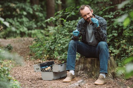smiling male scientist in latex gloves taking sample of dry leaf in test flask in forest