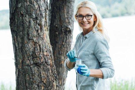 smiling female scientist in eyeglasses putting sample of bark of tree by tweezers in jar outdoors