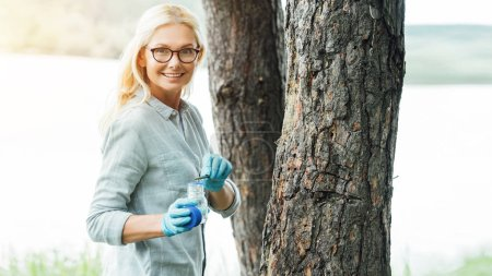Photo for Smiling female scientist in eyeglasses putting sample by tweezers in jar near trees outdoors - Royalty Free Image