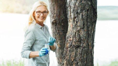 smiling female scientist in eyeglasses putting sample by tweezers in jar near trees outdoors