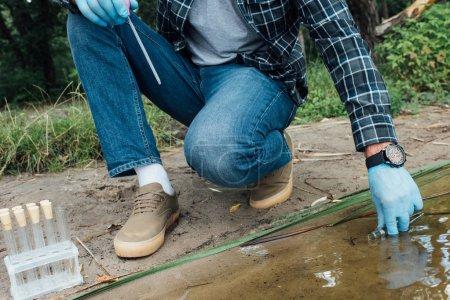 Photo pour Image recadrée du savant masculin en latex gants prélèvement d'échantillon d'eau dans le flacon d'essai à l'extérieur - image libre de droit