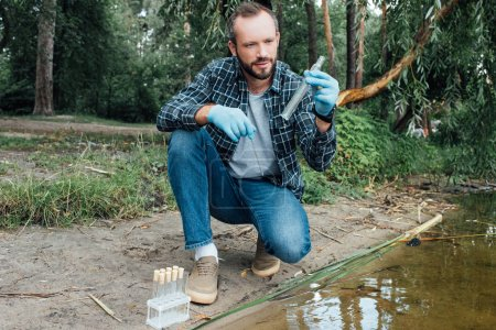 male scientist in latex gloves taking sample of water in test flask outdoors