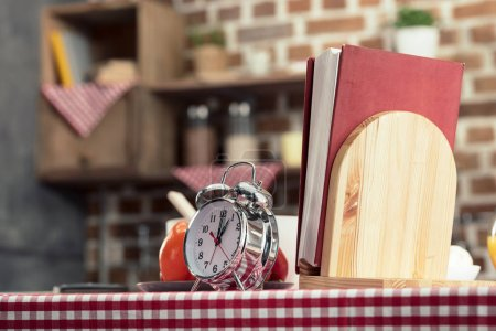 recipes book with alarm clock on cooking table at kitchen