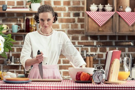 dangerous adult housewife with knife looking at camera at kitchen