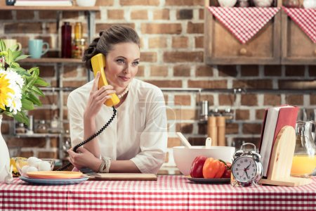 smiling adult housewife talking by retro wired phone and looking away at kitchen