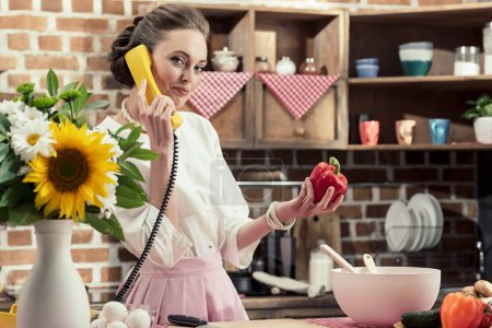 smiling adult housewife talking by retro wired phone and looking at camera at kitchen